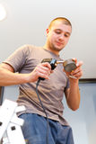 Electrician with Solder Gun. Electrician using solder gun working on ladder in house royalty free stock photos