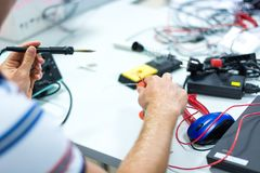 Electrician soldering wires. Closeup on working place with many electronic equipment Stock Photo