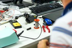 Electrician soldering wires. Closeup on working place with many electronic equipment Royalty Free Stock Photo