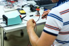 Electrician soldering wires. Closeup on working place with many electronic equipment Stock Images