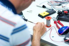Electrician soldering wires. Closeup on working place with many electronic equipment Royalty Free Stock Image