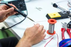 Electrician soldering wires. Closeup on working place with many electronic equipment Stock Photos