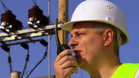 Electrician speaks the walkie-talkie close up. In summer day stock footage