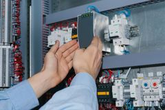 Electrician specialist checking low-voltage cabinet equipment Stock Photos