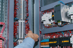 Electrician specialist checking low-voltage cabinet equipment. Photo of male electrical technician specialist checking indoor electric low-voltage cabinet Royalty Free Stock Photography