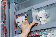 Electrician specialist checking low-voltage cabinet equipment. Photo of male electrical technician specialist checking indoor electric low-voltage cabinet Stock Photo
