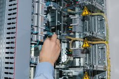Electrician specialist checking low-voltage cabinet equipment Stock Image