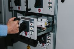 Electrician specialist checking low-voltage cabinet equipment Royalty Free Stock Images