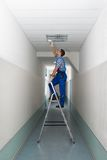 Electrician on stepladder installs lighting to the ceiling Stock Images