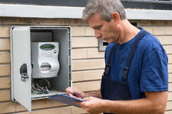 Electrician Taking Meter Readings. Portrait Of Electrician Worker Inspecting Electric Meter Royalty Free Stock Photos
