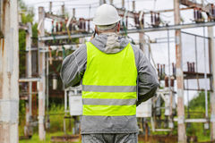 Electrician talking on the phone in electrical substation Royalty Free Stock Images