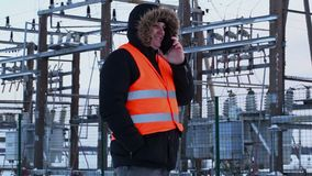 Electrician talking on smart phone at power plant in winter stock video