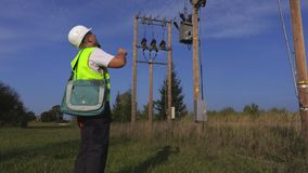 Electrician talking on smartphone and checking transformer. In summer day stock video