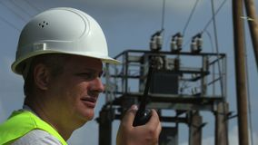 Electrician talks on walkie-talkie at high voltage transformator. In summer day stock footage