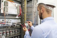 Electrician technician in fuse box. Maintenance engineer in control panel. Worker is testing automation equipment royalty free stock photo