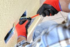 Electrician technician at work with safety equipment on a residential electrical system. Electrician technician at work blocks the cable between the clamps of a Stock Photography