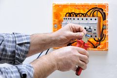 Electrician technician at work on a residential electric panel. Electrician technician working on a residential electric panel, cuts the cable with a cable stock images