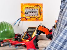 Electrician at work on cables with wire stripper. Electrician technician at work in a residential electric system uses the wire stripper with his hands Stock Images