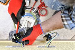 Electrician technician at work with safety equipment on a residential electrical system. Electrician technician at work blocks the cable between the clamps of a Royalty Free Stock Images