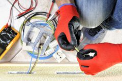 Electrician technician at work with safety equipment on a residential electrical system. Electrician technician at work prepares the cable with hands protected royalty free stock photos