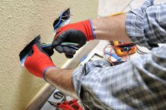Electrician technician at work with safety equipment on a residential electrical system. Electrician technician at work pulls the cables installed in a Stock Image