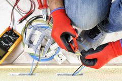 Electrician technician at work with safety equipment on a residential electrical system. Electrician technician at work with scissors on cable in a residential Stock Photo