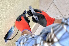 Electrician technician at work with safety equipment on a residential electrical system. Electrician technician at work sticks the cable between the clamps of a Royalty Free Stock Images