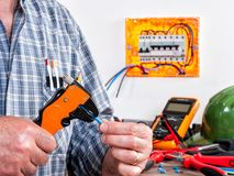 Electrician at work on cables with wire stripper. Electrician technician at work with wire stripper on cables in a residential electrical installation Stock Photo