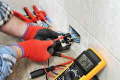Electrician technician working safely on a residential electrical system. Electrician technician with gloves and safety instruments he measures the voltage of a Stock Image