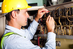 Electrician testing machine. Male electrician testing industrial machine royalty free stock photography