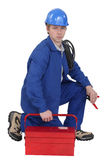 Electrician with a tool box. Electrician kneeling by a tool box stock photos