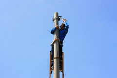 Electrician on the tower electric pole. Electrician stays on the tower electric pole and repairs a wire of the power line Royalty Free Stock Photo