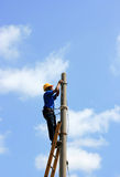 Electrician on the tower electric pole. Electrician stays on the tower electric pole and repairs a wire of the power line Royalty Free Stock Photography
