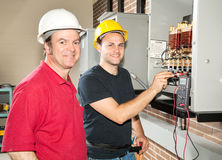Electrician in Training. Apprentice electrician and his instructor reading the voltage on a power distribution center Royalty Free Stock Images