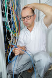 Electrician trying to find right cable. Electrician trying to find the right cable Stock Images