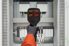 Electrician use thermo scan gun survey loosen cable by using temp gun. Electrician use thermo scan gun survey loosen cable, wiring and over load electric and Royalty Free Stock Photography