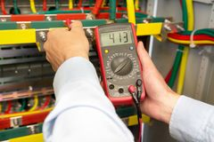 Electrician uses multimeter in fuse box. Engineer measuring voltage in electrical cabinet stock image