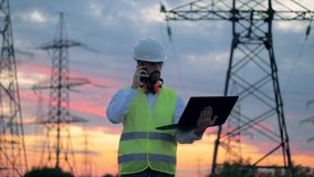 Electrician using cell phone near at the power line, electrical substation. 4K. Electrician using cell phone near at the power line, electrical substation stock footage