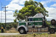 Live power Lines being Lifted, by Wooden Pole to Allow a Truck to go under with High Load. royalty free stock image