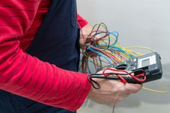 Electrician using voltmeter. When installing electric sockets on the wall in new home stock photos