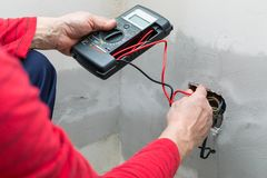 Electrician using voltmeter. When installing electric sockets on the wall in new home royalty free stock image
