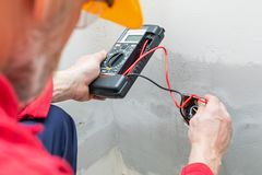 Electrician using voltmeter. When installing electric sockets on the wall in new home royalty free stock photography