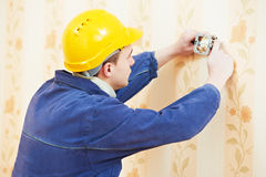 Electrician at wall outlet installation Stock Images