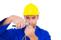 Electrician wearing hard hat while cutting wire with pliers Stock Images