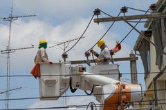 The electrician went up to the crane basket. To install the power pole Stock Photo