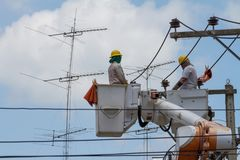 The electrician went up to the crane basket. To install the power pole Stock Photos
