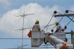 The electrician went up to the crane basket. To install the power pole Royalty Free Stock Photos