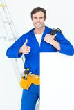 Electrician with wire and bill board gesturing thumbs Royalty Free Stock Photos