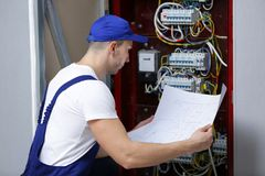 Electrician with wiring diagram checking connections Royalty Free Stock Photos