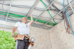 Electrician wiring garage ceiling. Electrician wiring a garage ceiling stock photography